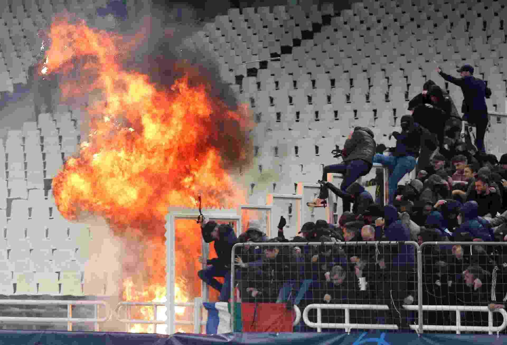 Torcedores do Ajax se protegem de ataque de torcedores do AEK Atenas antes de jogo na Grécia - Costas Baltas/Reuters