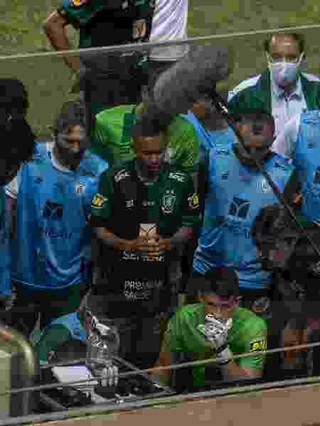 Jogadores do América-MG acompanham o final do jogo da Chape pela TV, na beira do gramado do Independência - GLEDSTON TAVARES/FRAMEPHOTO/ESTADÃO CONTEÚDO - GLEDSTON TAVARES/FRAMEPHOTO/ESTADÃO CONTEÚDO