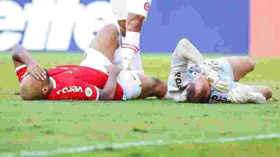 Rodrigo Moledo e Marcelo Lomba ficam caídos após choque durante a partida entre Internacional e CSA  - Pedro H. Tesch/AGIF