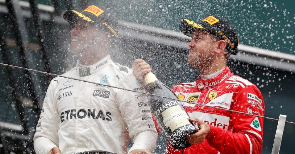 Sebastian Vettel, da Ferrari, joga champanhe em Lewis Hamilton, da Mercedes, após o GP da China