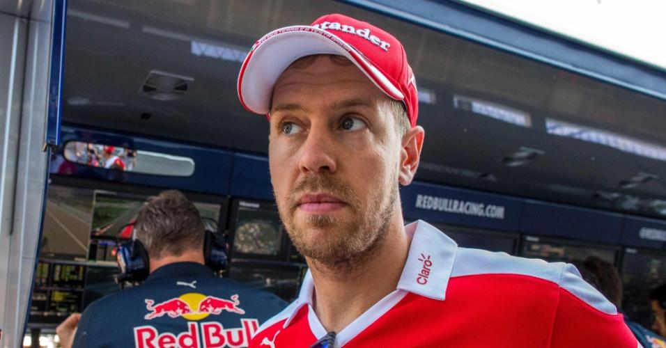 Sebastian Vettel, da Ferrari, caminha pelo grid de cara fechada após conversar com Christian Horner, chefe da Red Bull
