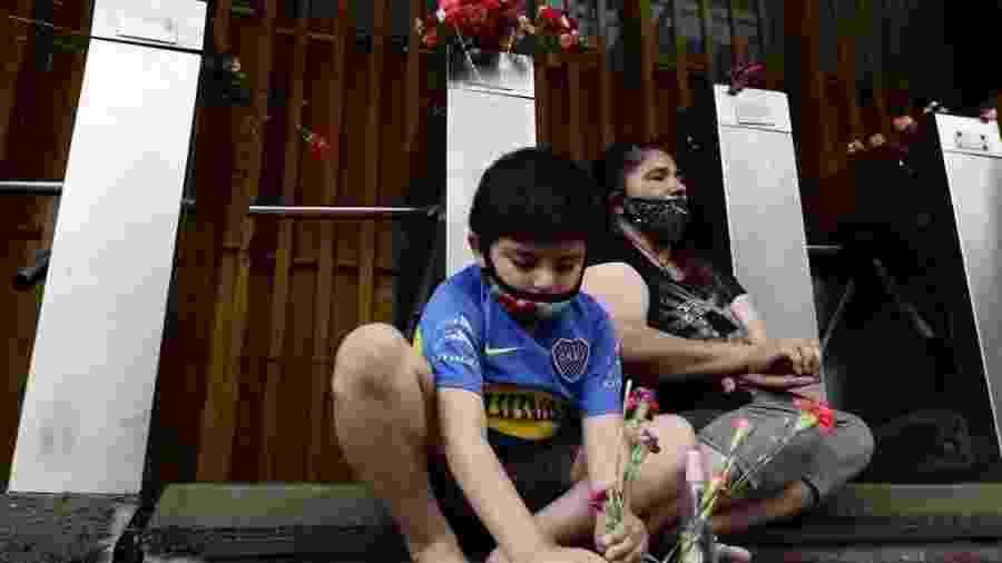 25.11.2020 - Criança posiciona flores na entrada do estádio La Bombonera, do Boca Juniors, em Buenos Aires, como homenagem a Maradona - Alejandro Pagni/AFP