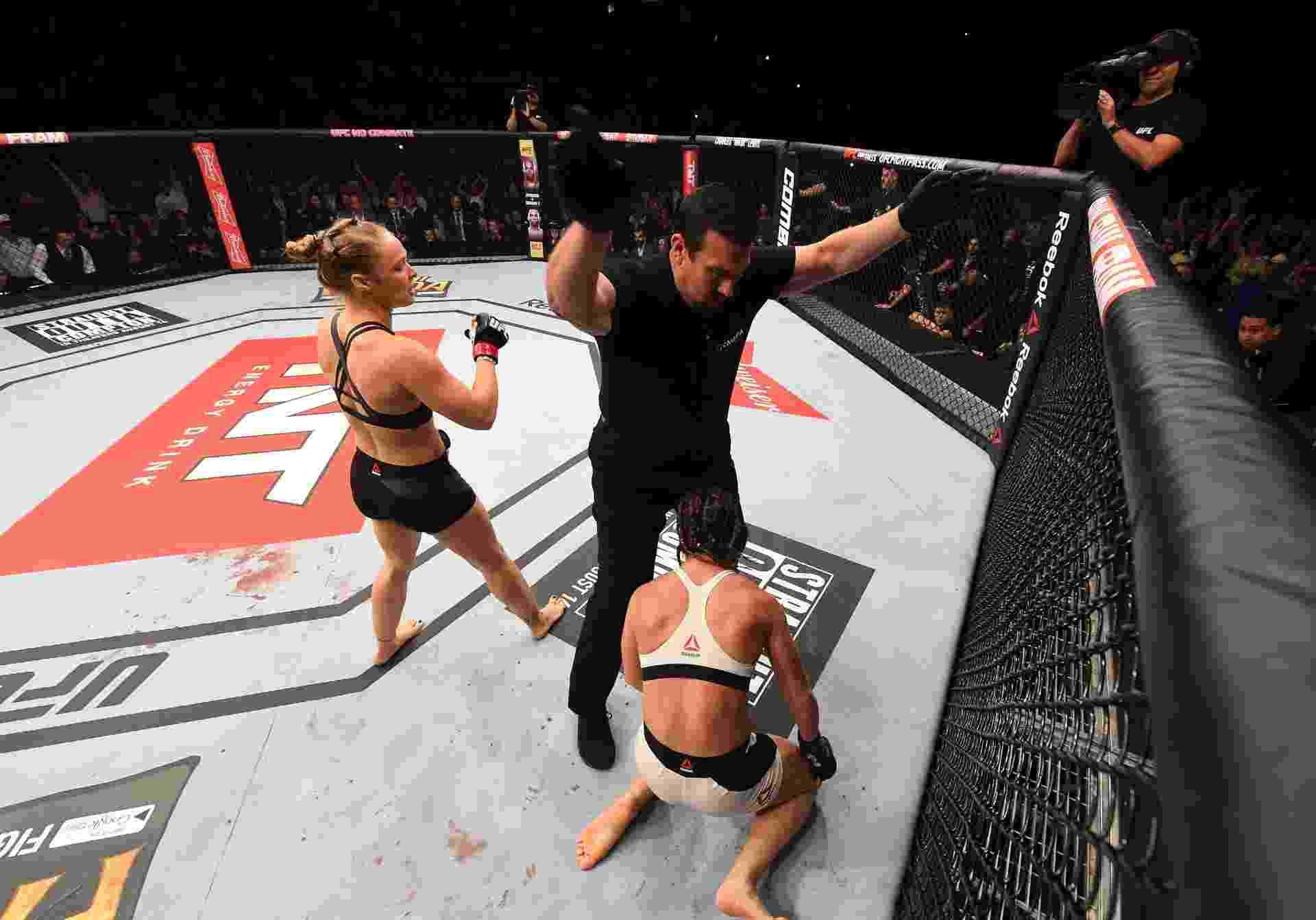 Ronda Rousey (esq.) comemora após nocautear Bethe Correia, que fica ajoelhada no chão, na luta principal do UFC 190 - Josh Hedges/Zuffa LLC UFC
