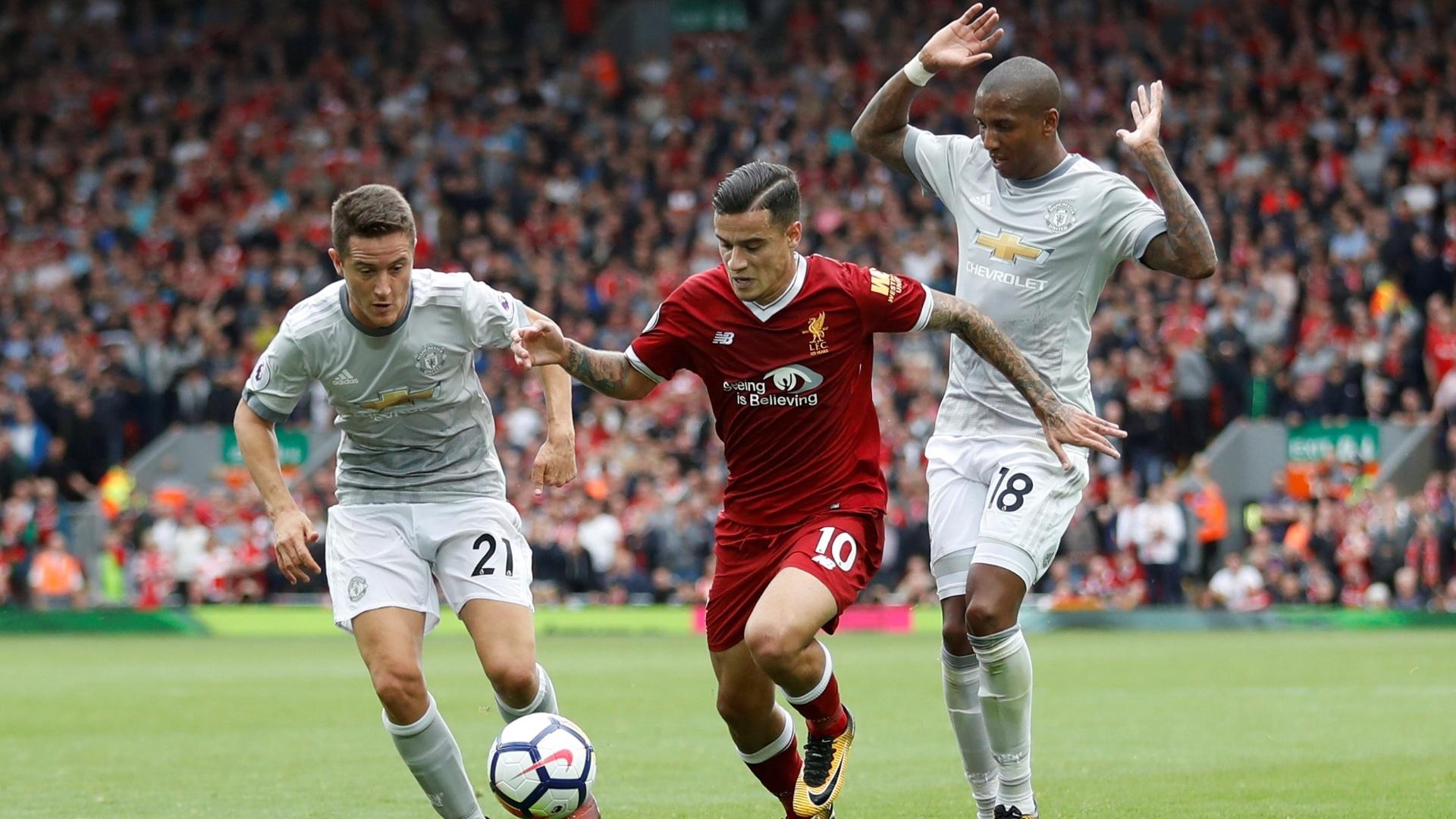 Coutinho (centro), do Liverpool, tenta uma jogada contra o Manchester United