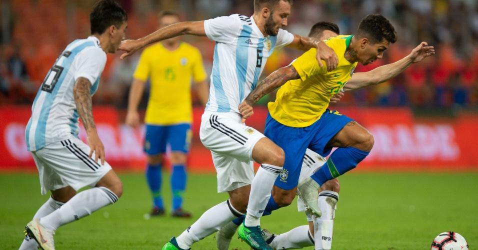 Roberto Firmino encara a marcação de Pezzella no amistoso entre Brasil e Argentina