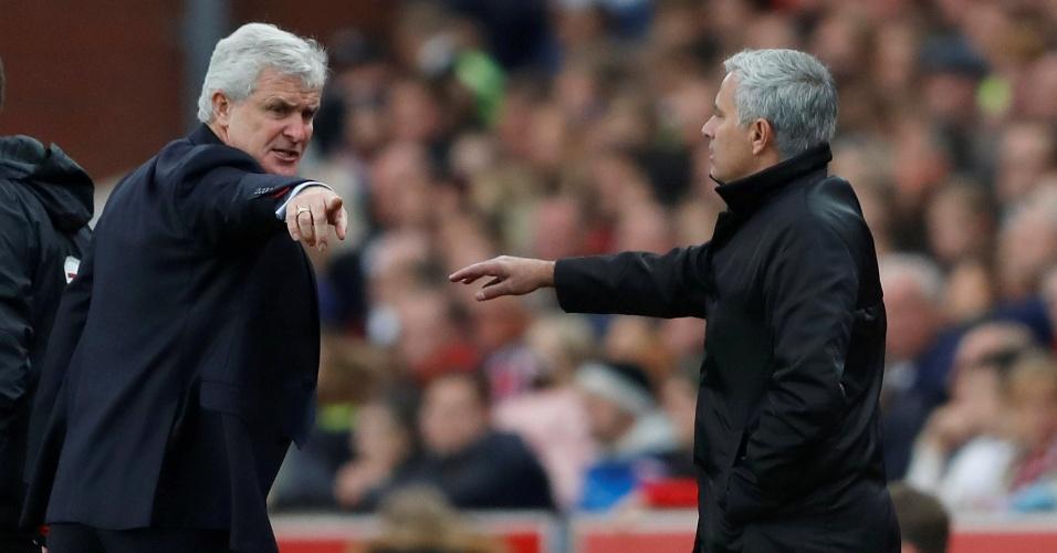 O treinador do Stoke City Mark Hughes aponta para José Mourinho voltar para sua área técnica após desentendimento entre os dois