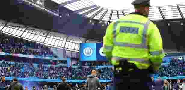 Policial assiste à festa de torcedores invasores dentro do campo do Etihad Stadium, em Manchester - Clive Brunskill/Getty Images - Clive Brunskill/Getty Images