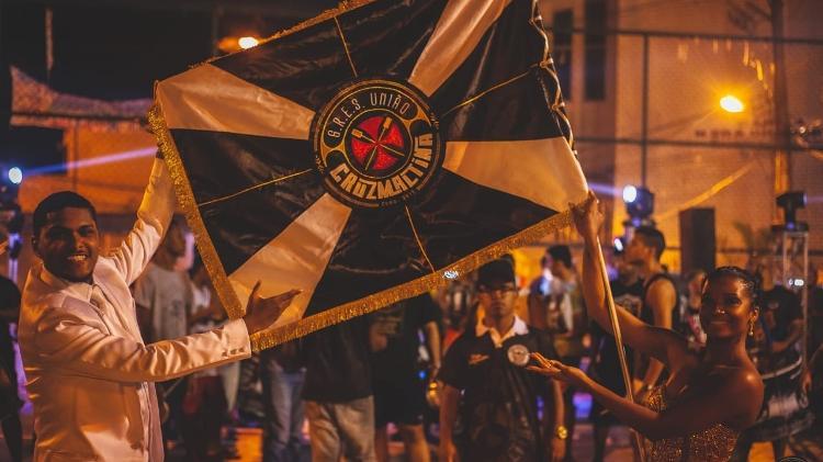 Mestre-sala e porta-bandeira exibem o pavilhão da União Cruzmaltina, a escola de samba dos vascaínos - Close Produtora / União Cruzmaltina