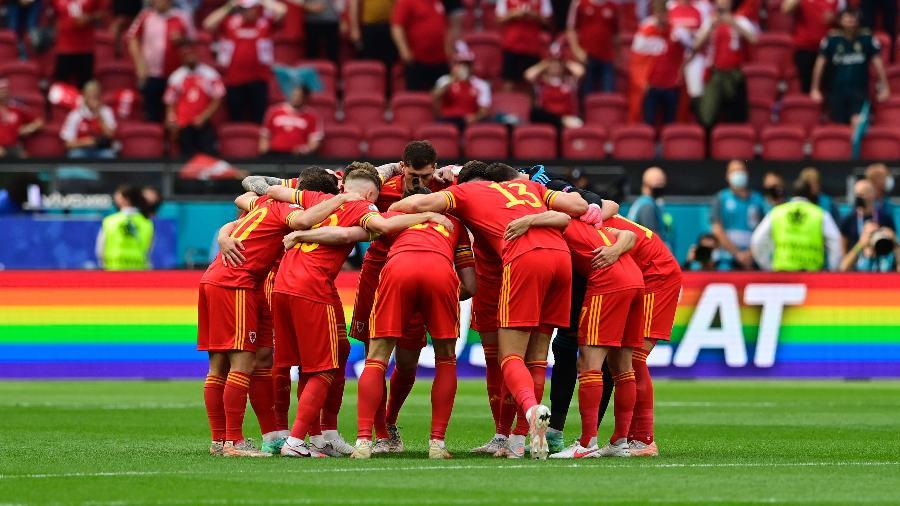 Jogadores do País de Gales reunidos antes do duelo com a Dinamarca. Ao fundo, patrocínio faz ação contra nova lei húngara  - Olaf Kraak - Pool/Getty Images