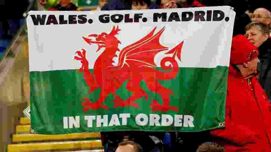 """Torcedores seguram a bandeira com os dizeres """"Gales. Golfe. Madrid. Nesta ordem"""" - ANDREW BOYERS / REUTERS"""
