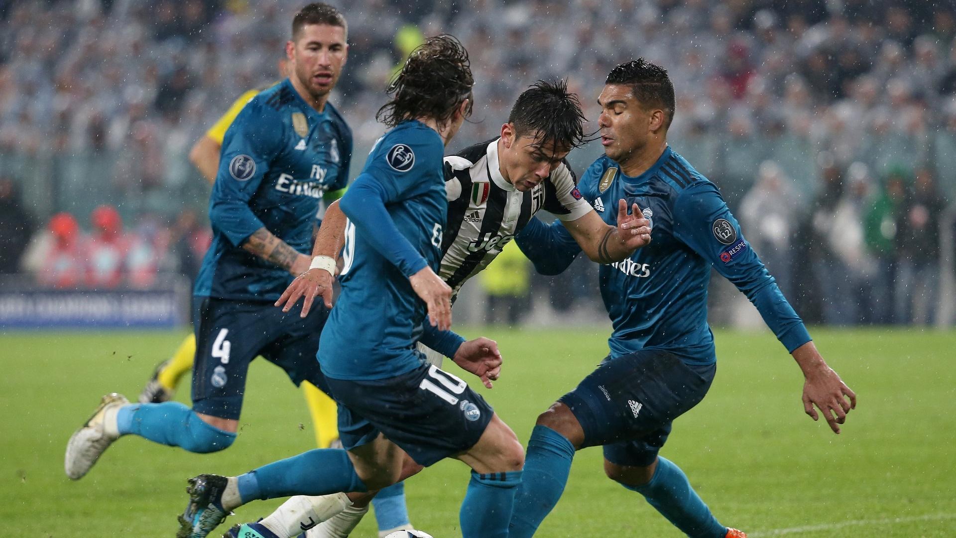 Dybala tenta passar pela marcação dupla de Casemiro e Modric no jogo entre Juventus e Real Madrid