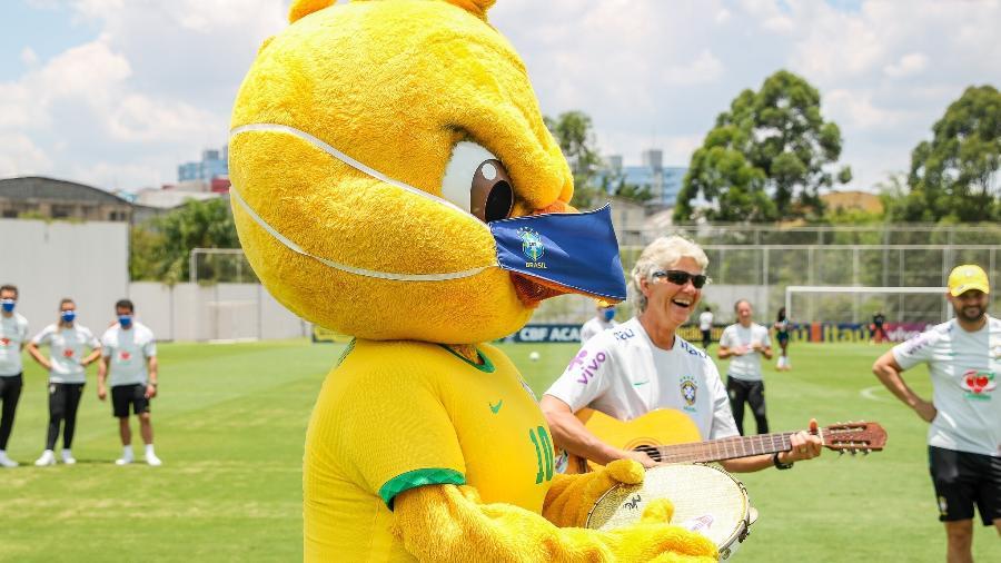 Canarinho Pistola toca pandeiro, e Pia Sundhage, técnica da seleção brasileira, violão, durante treino em 26/11 - Mariana Sá/CBF