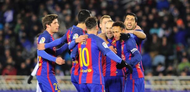 Neymar é abraçado por companheiros nesta quinta-feira (19) após marcar gol contra a Real Sociedad: enquanto isso, multa de R$ 200 milhões era decidida em Brasília.