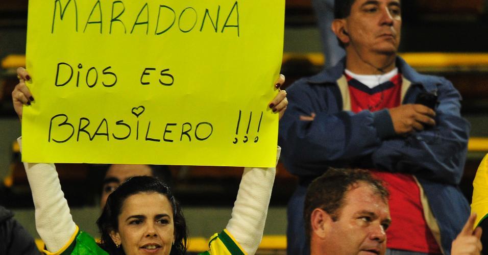 Torcedora brasileira segura cartaz com a frase: