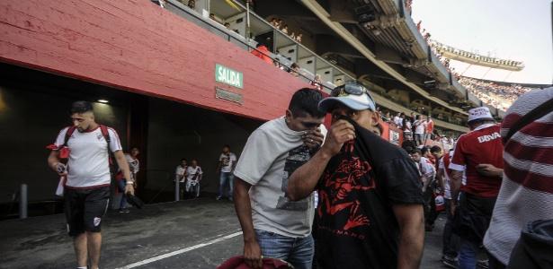 Torcedores cobrindo o rosto após ataque ao ônibus do Boca  - JAVIER GONZALEZ TOLEDO / AFP