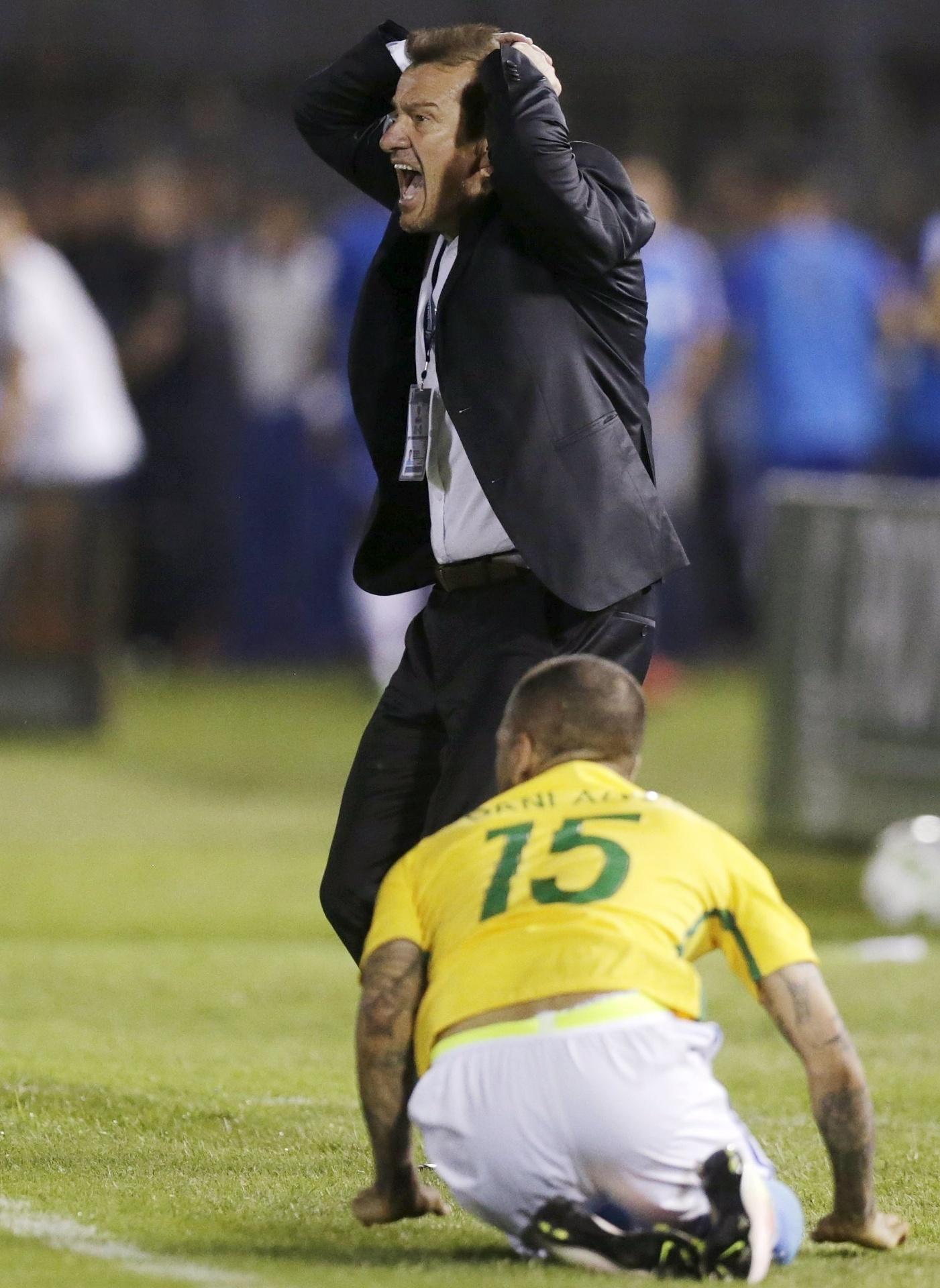 Dunga fica nervoso ao orientar a seleção e Daniel Alves cai ajoelhado aos pés do treinador em jogo contra o Paraguai