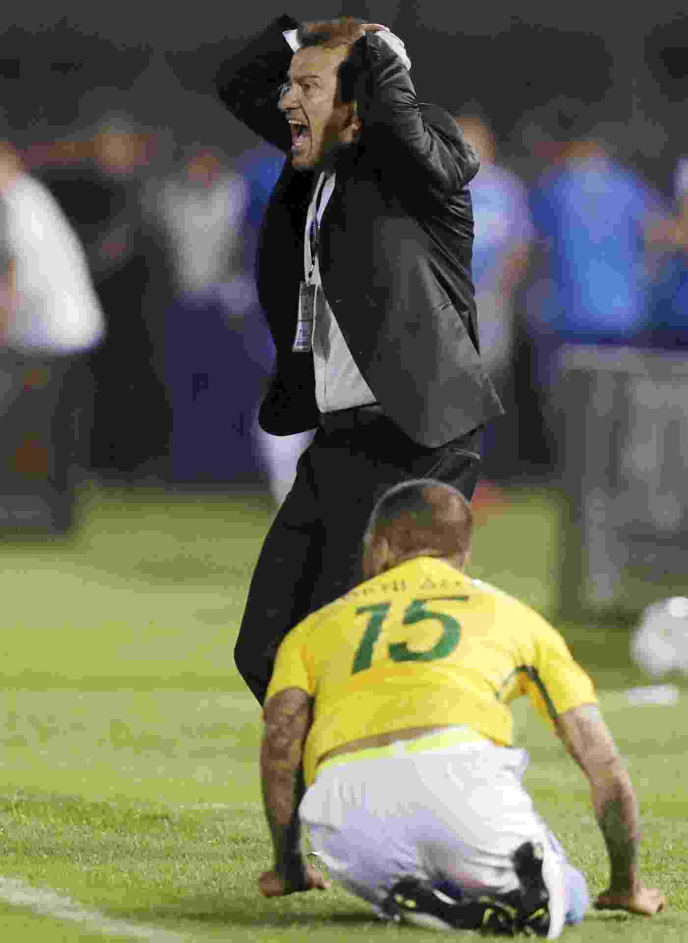 Dunga fica nervoso ao orientar a seleção e Daniel Alves cai ajoelhado aos pés do treinador em jogo contra o Paraguai - REUTERS/Jorge Adorno