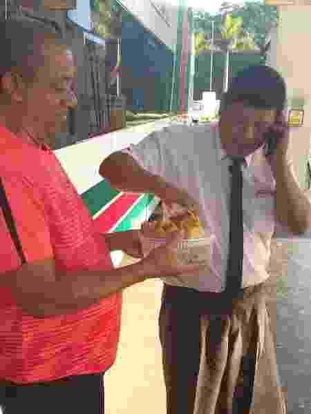 Torcedor do Flamengo serve bolo para um dos motoristas no ônibus que vai até Lima - Diego Salgado/UOL Esporte