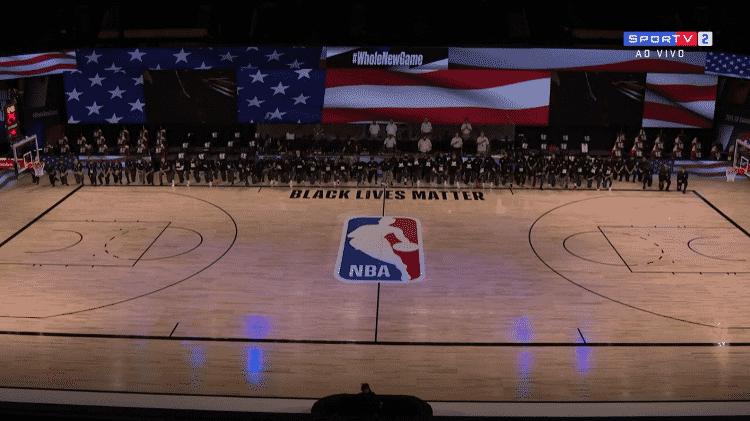 Jogadores e comissão técnica se ajoelham durante hino dos estados unidos antes de Utah Jazz x New Orleans Pelicans primeiro jogo da volta da NBA - Reprodução/SporTV - Reprodução/SporTV