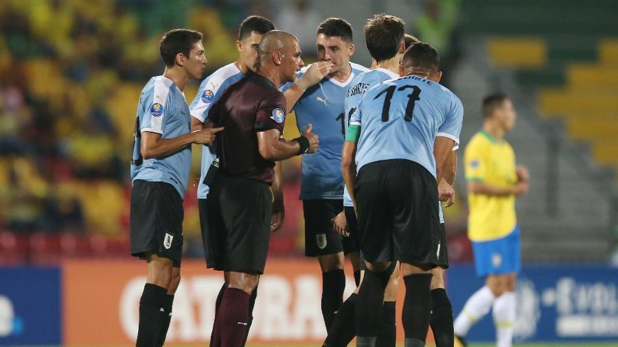 Jogadores do Uruguai cercam o árbitro do duelo com o Brasil pelo Pré-Olímpico - Luisa Gonzalez/Reuters