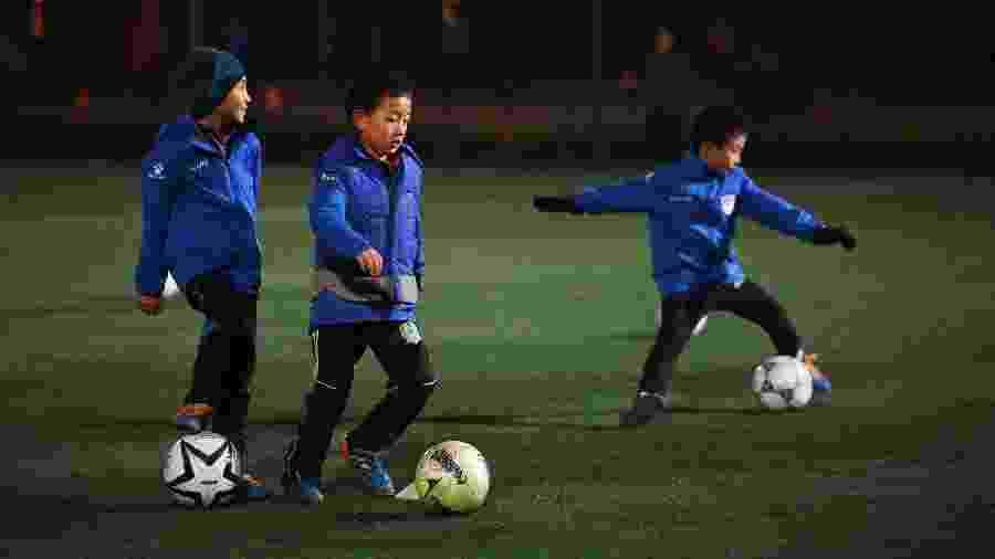 Crianças chinesas treinam futebol - Greg Baker / AFP