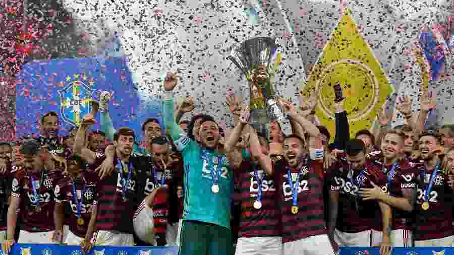 Jogadores do Flamengo comemoram com a taça de campeão brasileiro, após vitória sobre o Ceará - Thiago Ribeiro/AGIF
