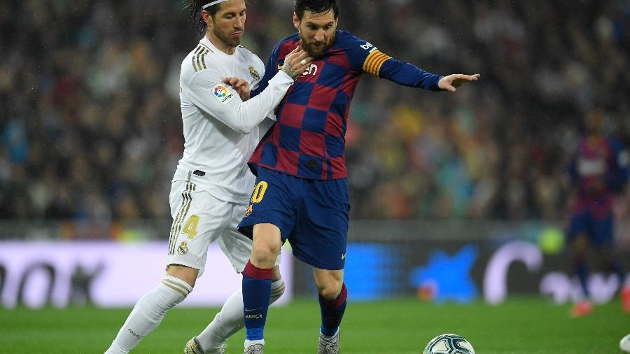 O zagueiro Sergio Ramos, do Real Madrid, e Messi, do Barcelona, em lance pelo clássico do Campeonato Espanhol - OSCAR DEL POZO / AFP