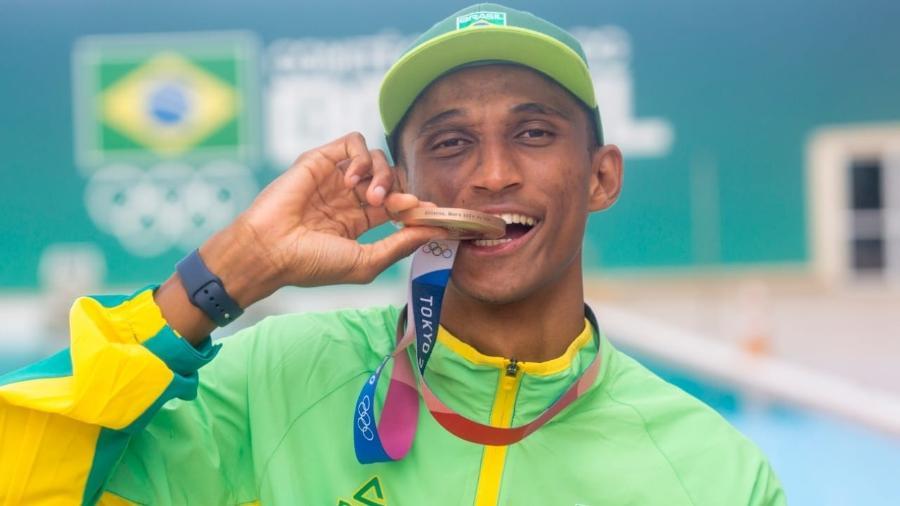 Alison Santos, o Piu, morde a medalha de bronze que conquistou nos 400 m dos Jogos Olímpicos de Tóquio - Daniel Ramalho / COB