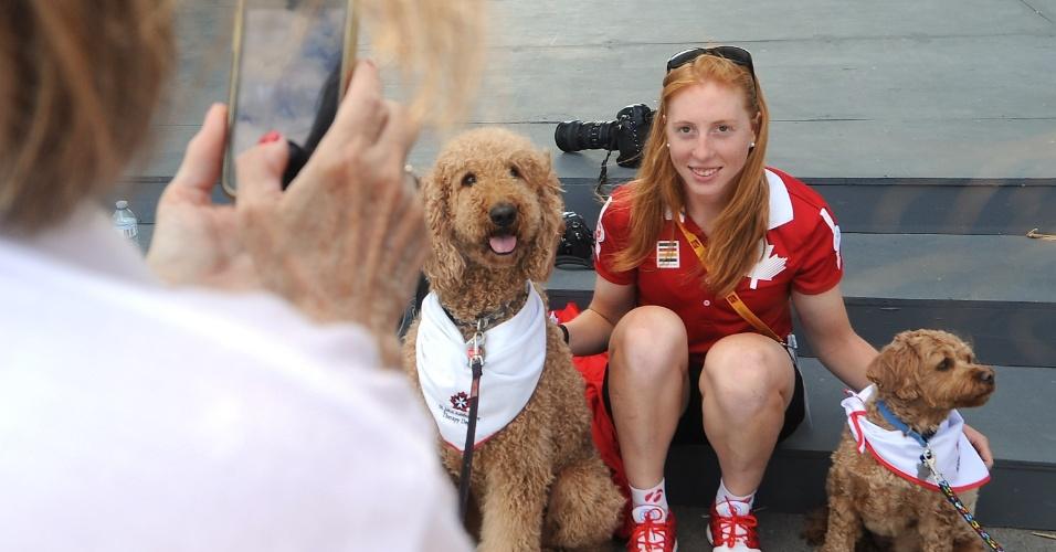 A ciclista canadense Allison Beveridge posa para foto com Enzo e Mr. Darcy (à esquerda)