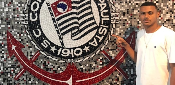 Matheus Mello posa ao lado do escudo do Corinthians após acerto - Divulgação