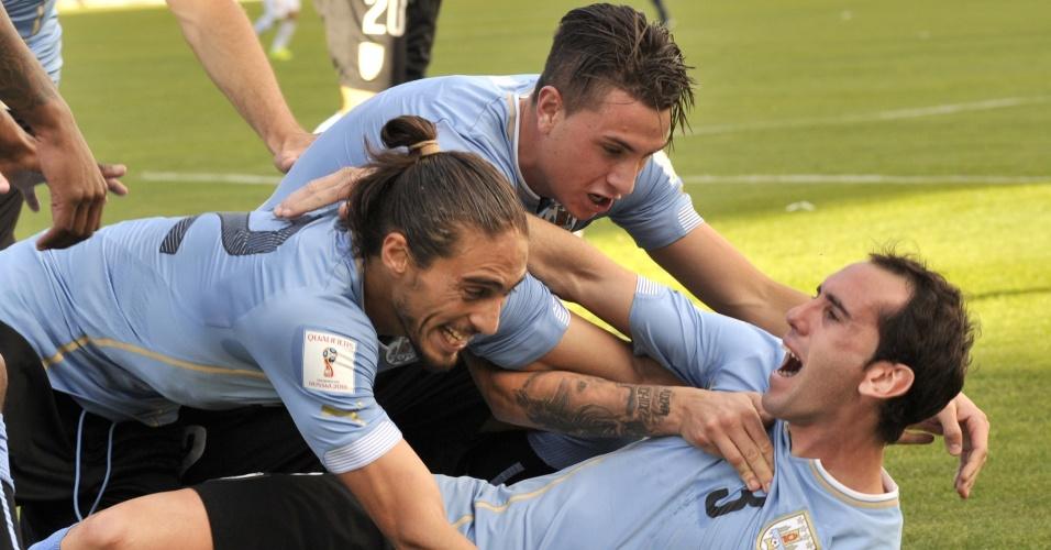 Martin Caceres e Gimenez comemoram o gol do Uruguai junto com o zagueiro Diego Godin