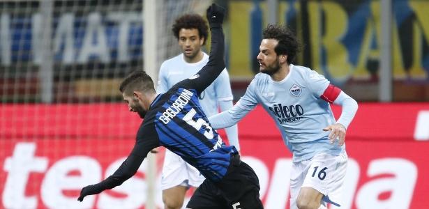 Felipe Anderson observa Gagliardini e Parolo em dividida durante a partida