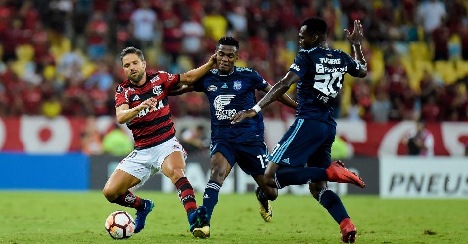 Diego encara a marcação de dois jogadores do Emelec em jogo do Flamengo na Libertadores