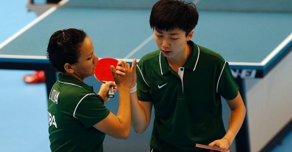 Ligia Silva e Lin Gui se cumprimentam durante a partida mista de tênis de mesa