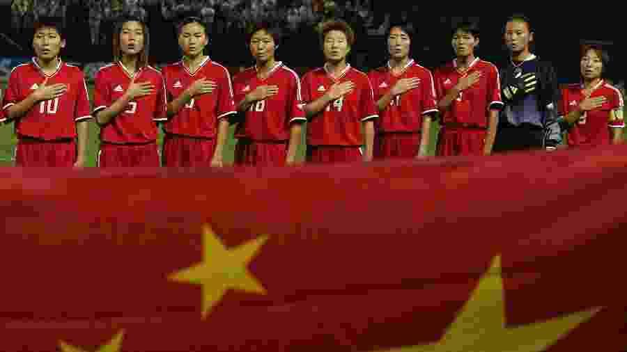 Seleção de futebol da China canta hino nacional antes de partida contra a Rússia pela Copa do Mundo feminina de 2003, nos Estados Unidos - Ben Radford/Getty Images