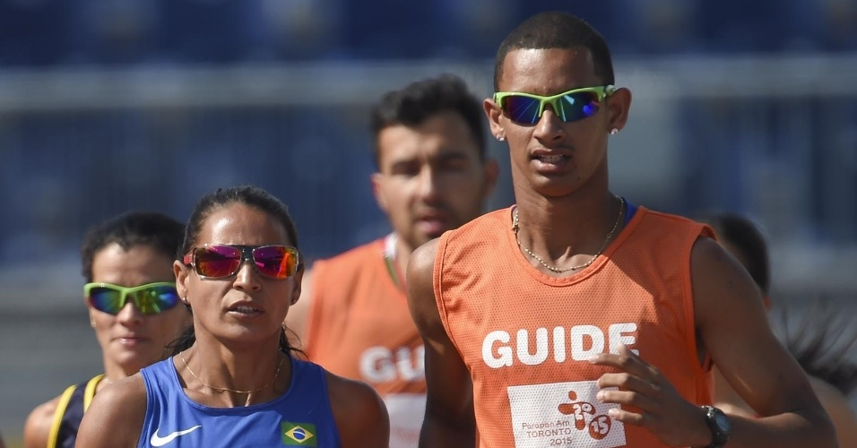 Renata Bazone e seu guia, Fernando correm para medalha de prata nos 1500 metros. A evolução dos atletas tem dificultado a prospecção destes profissionais
