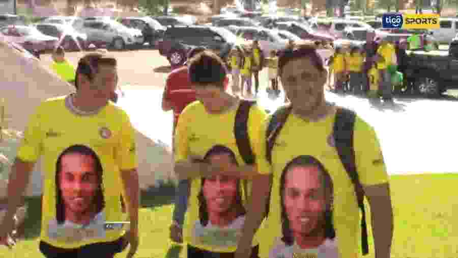 Camisa patrocinada por ONG na chegada de Ronaldinho Gaúcho ao Paraguai é a mesma usada em passaporte falso - Reprodução/Tigo Sports