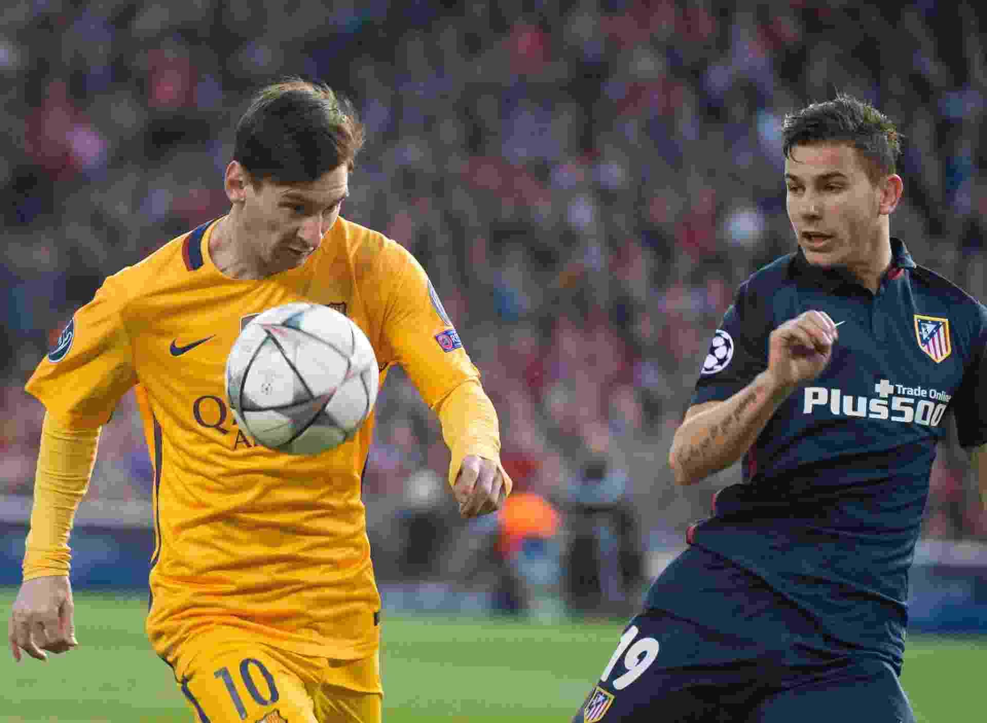 Lionel Messi conduz a bola acompanhado pela marcação de Hernandez na partida entre Atlético de Madri e Barcelona pela Liga dos Campeões - Curto De La Torre/AFP Photo