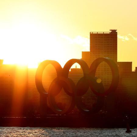 Sol atrás dos aros olímpicos no parque Odaiba em 24 de março em Tóquio no dia em que os Jogos Olímpicos de 2020 foram adiados - Clive Rose/Getty Images
