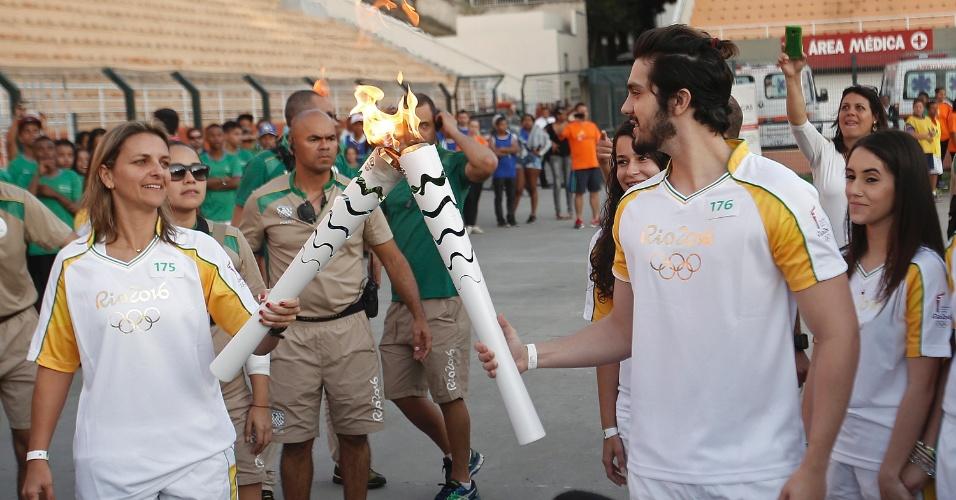 São Paulo - Juliana Cabral, zagueira da seleção brasileira de futebol que ganhou a medalha de prata nas Olimpíadas de Atenas-2004, recebe a chama olímpica das mãos do cantor Luan Santana