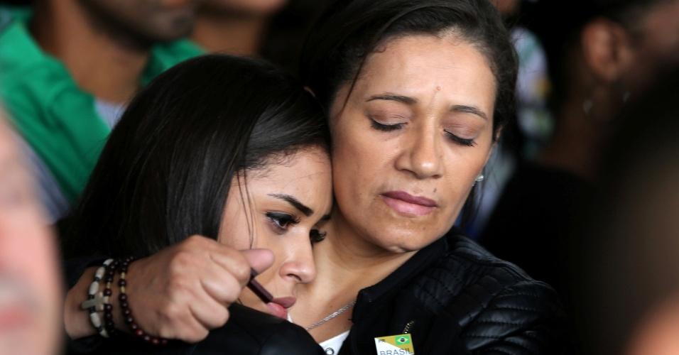 Familiares se consolam durante chegada de aviões da FAB ao Aeroporto de Chapecó