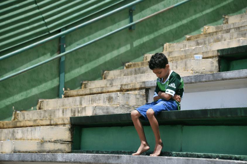Garoto lamenta o acidente com o time da Chapecoense em homenagem na Arena Condá, em Chapecó