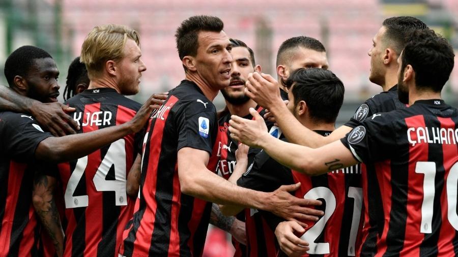 Jogadores do Milan comemoram gol contra o Genoa em partida válida pelo Campeonato Italiano - Filippo MONTEFORTE / AFP