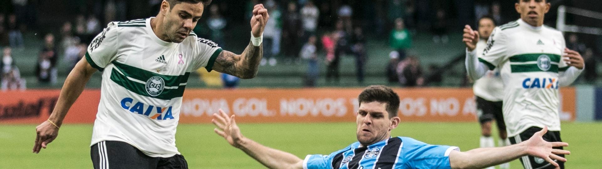 Henrique carrega a bola e é marcado por Ramiro no jogo entre Coritiba e Grêmio