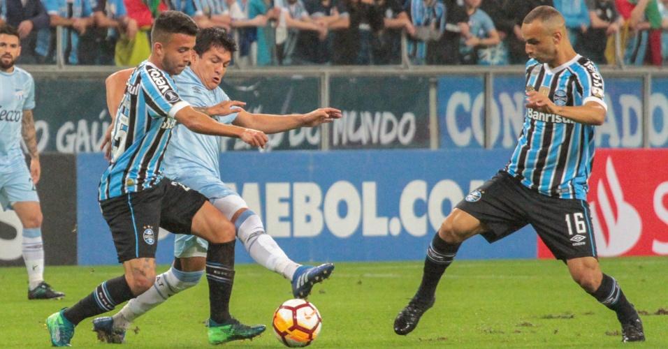 Thaciano e Matheus Henrique apertam marcação durante duelo entre Grêmio e Atlético Tucumãn