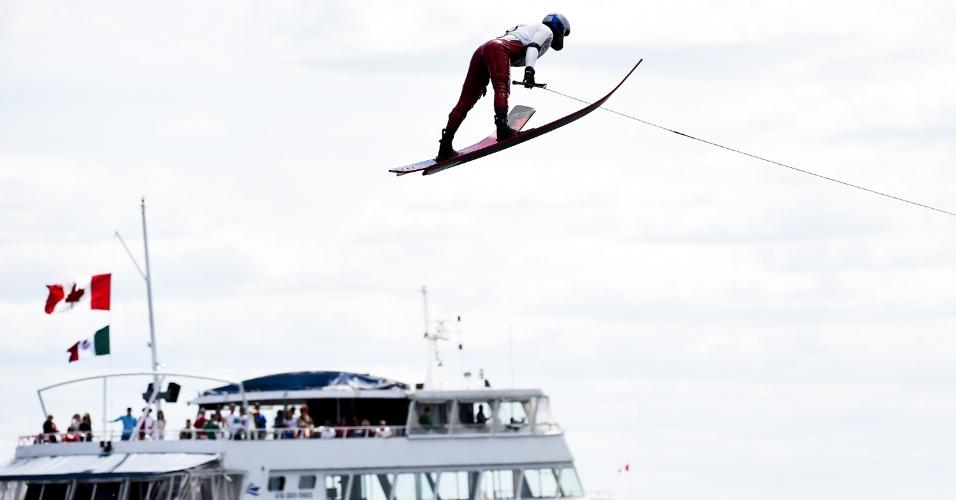 Jaret Llewellyn, do Canadá, voa com navio ao fundo durante prova do esqui aquático