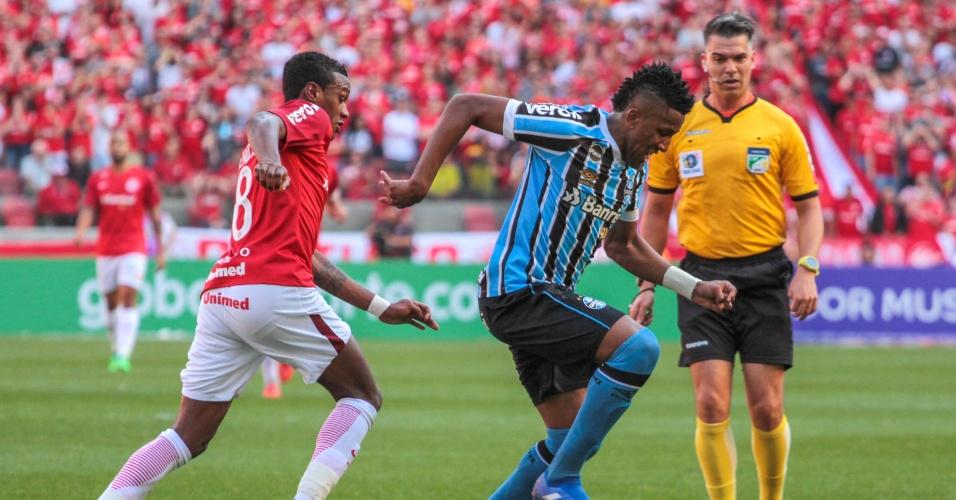 Cortez carrega a bola e é seguido por Edenilson durante jogo entre Internacional e Grêmio