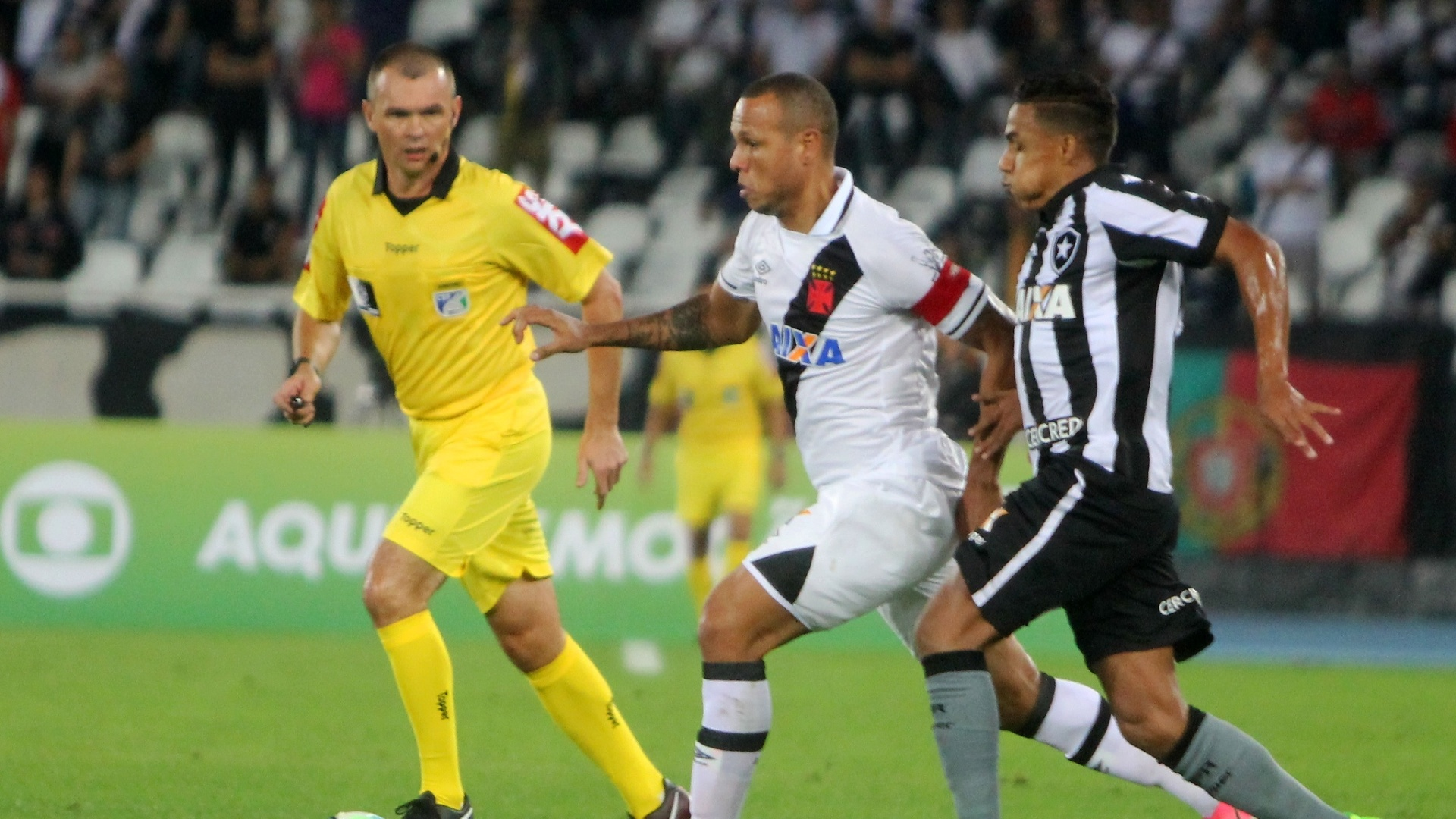Observado pelo árbitro Leandro Vuaden, Luís Fabiano conduz a bola na partida Botafogo x Vasco