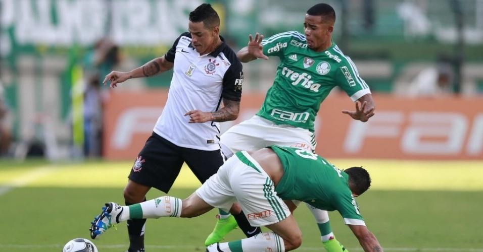 03.abril.2016 - Giovanni Augusto, meia do Corinthians, tenta escaparde livrar da marcação dos jogadores do Palmeiras no clássico no Pacaembu