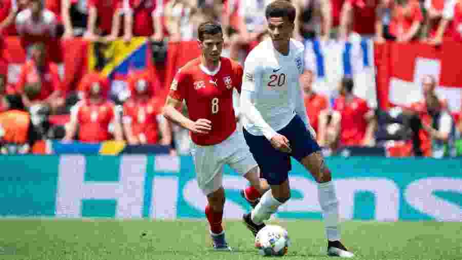 Dele Alli conduz a bola acompanhado de perto pela marcação de Michael Lang na partida entre Suíça e Inglaterra pela Liga das Nações - TF-Images/Getty Images